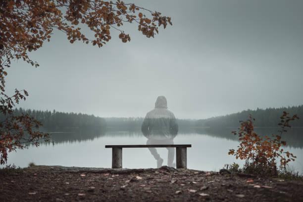 ein transparente mann auf einer bank sitzend und mit blick auf den see. hinten sie ansicht von. herbst-thema - abwesenheit stock-fotos und bilder