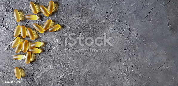 Transparent matte yellow gel capsules of omega and fish oil on a gray concrete background. The concept of a healthy lifestyle, the treatment of dietary supplements, naturopathy and alternative medicine.