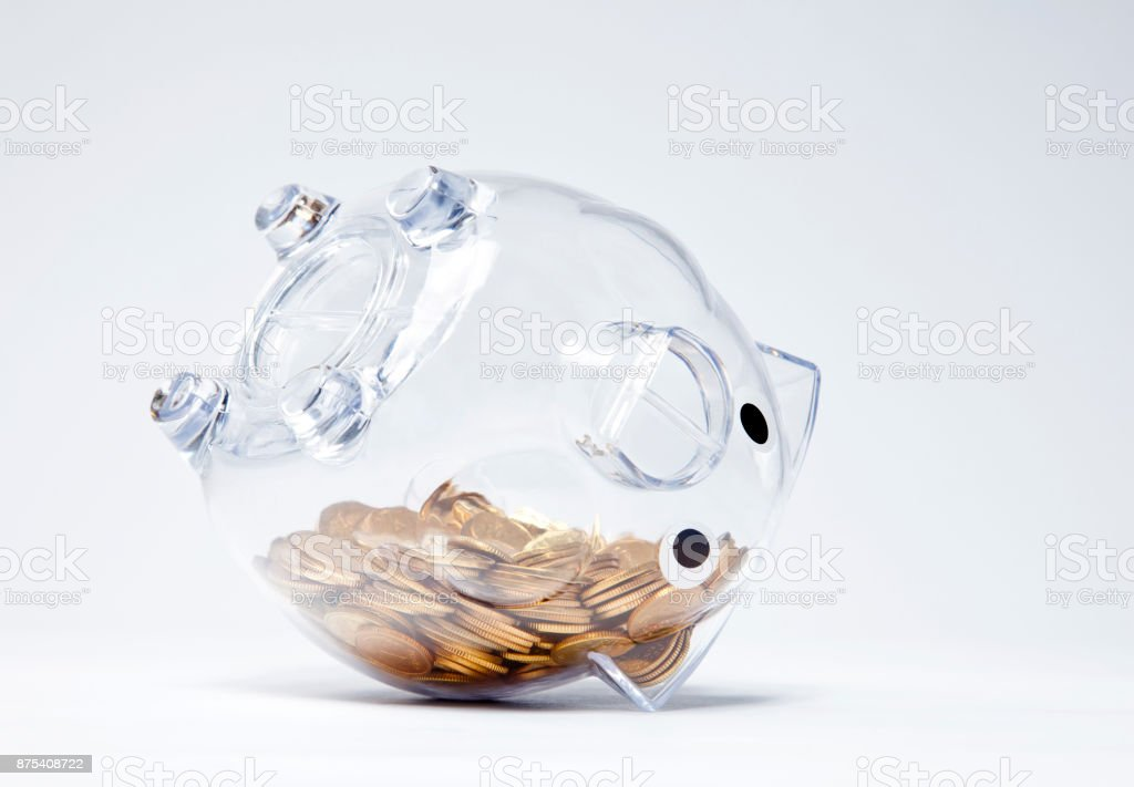 Transparent piggy bank with golden coins upside down stock photo