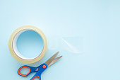 istock Transparent roll of scotch and scissors on light pastel blue background. Closeup. Empty place for text. Top view. 1140774060