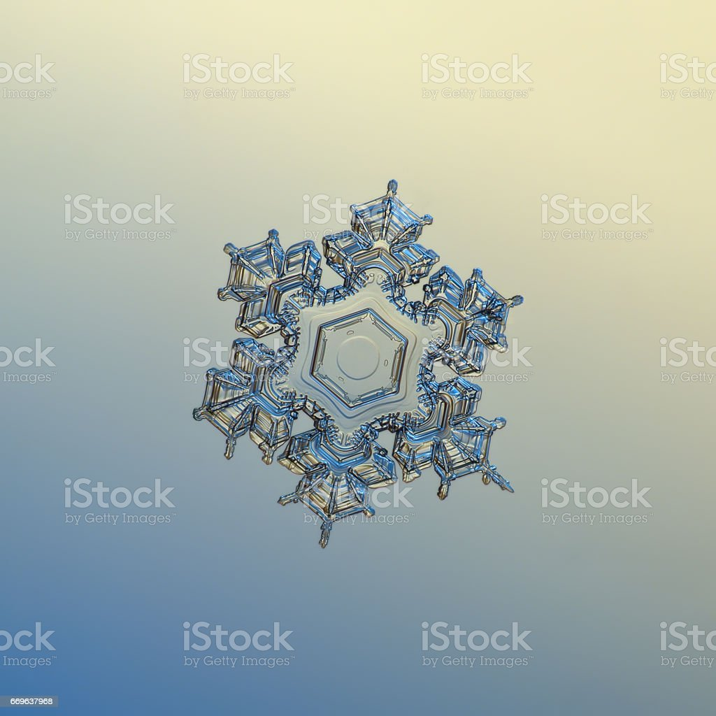 Transparent snowflake sparkling on pale yellow - blue gradient background stock photo