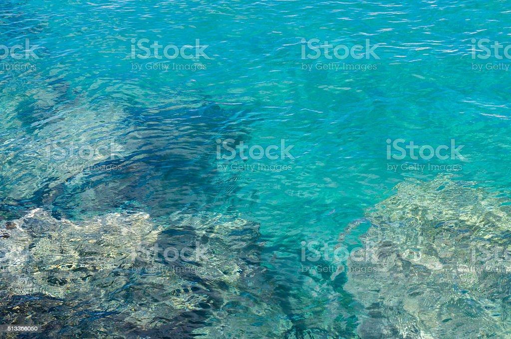Transparente türkisfarbenen Wasser in der Nähe der felsigen Küste – Foto