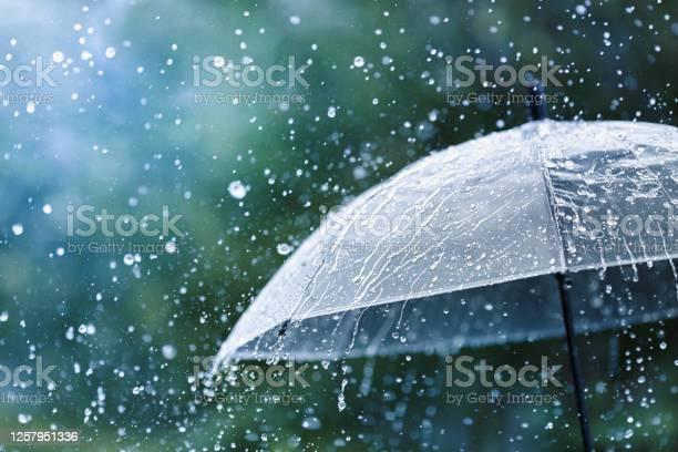 Photo of Transparent umbrella under rain against water drops splash background. Rainy weather concept.