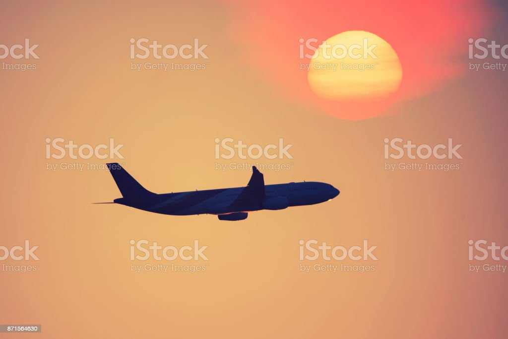 Transport aircraft in the sky at sunset stock photo