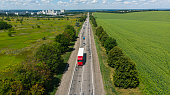 Transport logistics background. Commercial truck and cars driving by the highway. View above from drone.