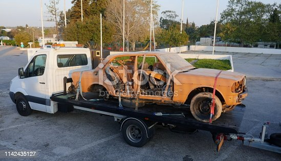Transporting an old, broken, rusty car with a tow truck