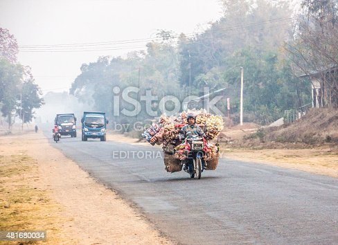 Loikaw, Myanmar - February 7, 2015: A street seller is driving his motorbike along a road near Loikaw, Myanmar. The bike is loaded with his merchandise.