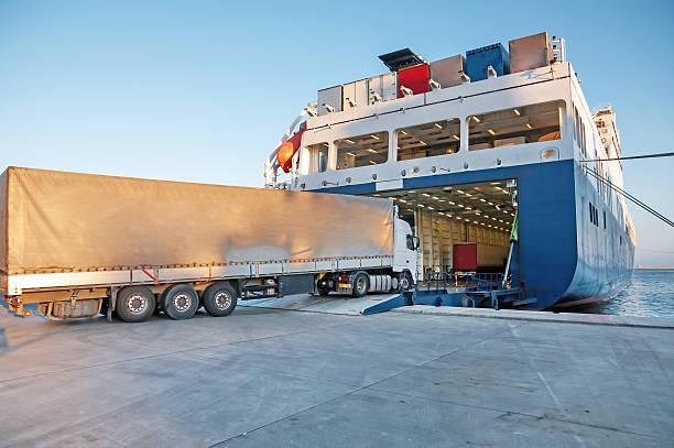 transport truck entering a transport shipping barge - veerboot stockfoto's en -beelden