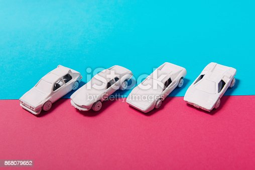 Minimalist pastel color image with white toy cars and vehicles from different perspectives. Color surge and white cars representing traffic, commuting, transportation and modern living. Lots of copy space on image.