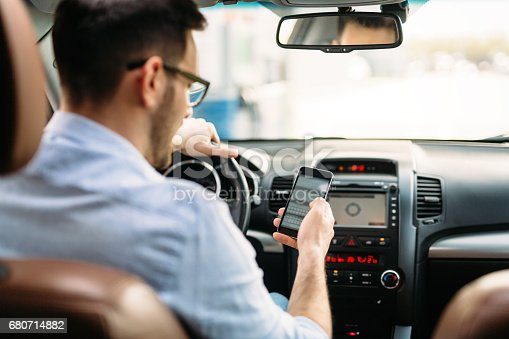 istock transportation concept - man using phone while driving the car 680714882