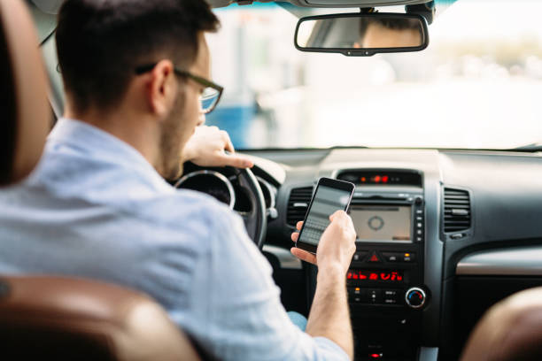 transportation concept - man using phone while driving the car - text messaging stock photos and pictures