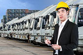 Transportation engineer with trucks of a transporting company in a row