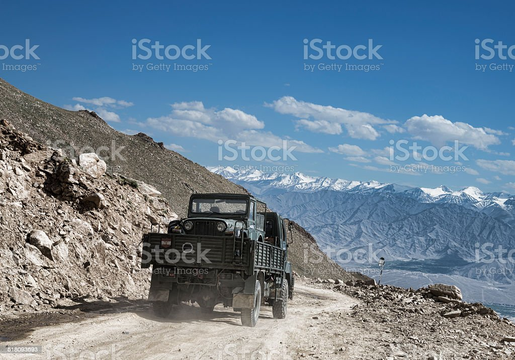 Transportation of army car on a truk among mountains stock photo
