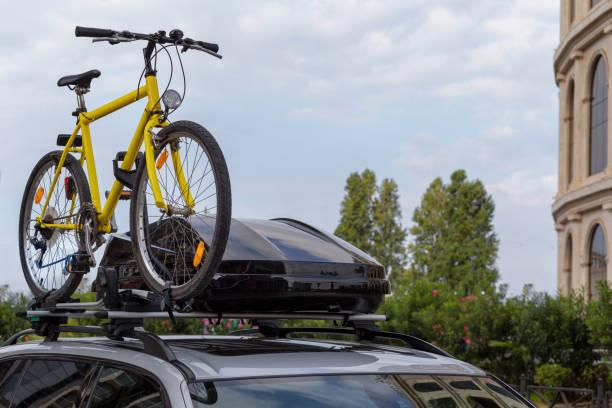 transport von fahrrädern auf dem dach des autos. konzept: eine autoreise mit dem fahrrad - fahrradhalter stock-fotos und bilder