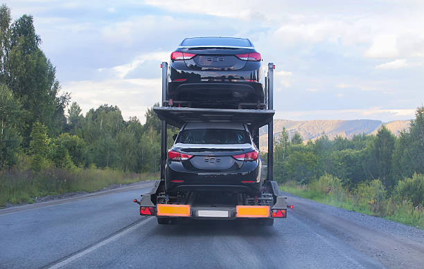transportation of car on semi-trailer transportation of car on semi-trailer on country highway carrying stock pictures, royalty-free photos & images