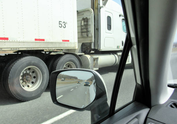 "Transportation, ""Passing a Semi; Rear View Mirror"" Transportation...Here we are looking out of the driver side window in a car, as a huge semi, tractor trailer truck, roars past on the left side. alongside stock pictures, royalty-free photos & images"