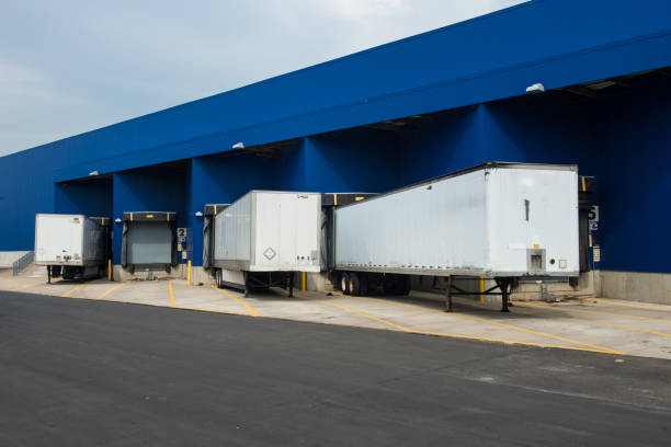 Transportation service delivery station warehouse with trucks Transportation service delivery station. Big distribution warehouse with gates for loads and trucks distribution center stock pictures, royalty-free photos & images