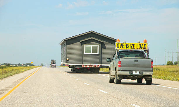 Transporting a House Trailer Down a Highway on Flatbed Truck Horizontal image of a house trailer, or mobile home, being transported down a divided highway on a flatbed truck. A pilot vehicle is visible behind the flatbed to warn approaching vehicles of the dangerous width of the load. manufactured housing stock pictures, royalty-free photos & images