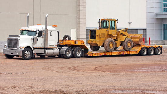 Side view of a parked semi truck equipped with a drop bed trailer ready to transport a pay loader.