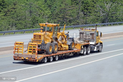 Elevated rear quarter view of a flatbed semi truck on a highway transporting a road grader.