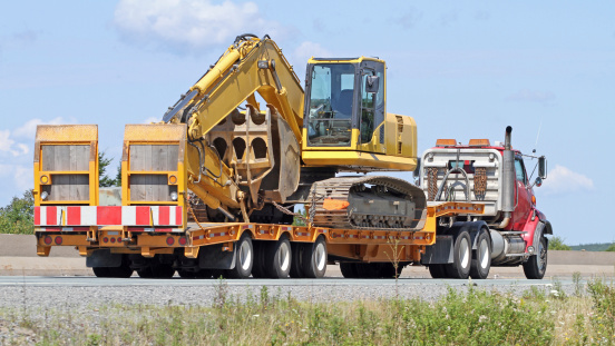Rear quarter view of a flatbed semi truck on a highway transporting an excavator.