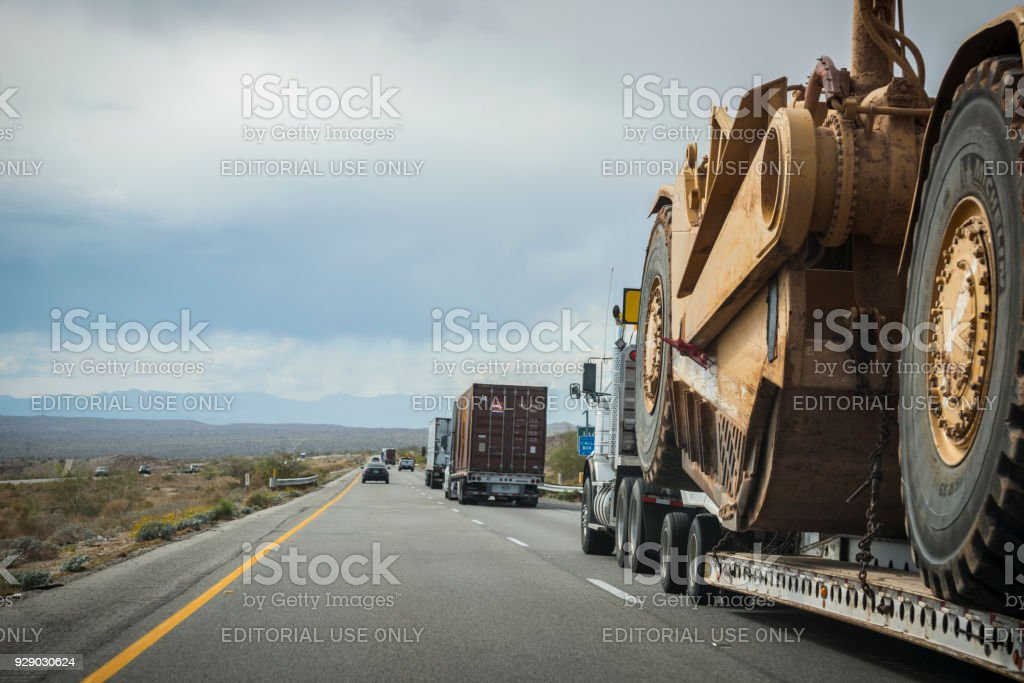 Transporting large Caterpillar wheel tractor-scraper on highway stock photo