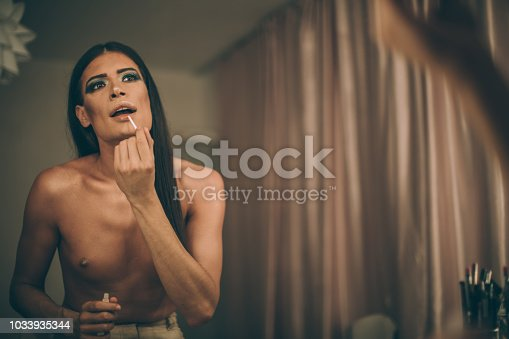 Transsexual man putting make up at home