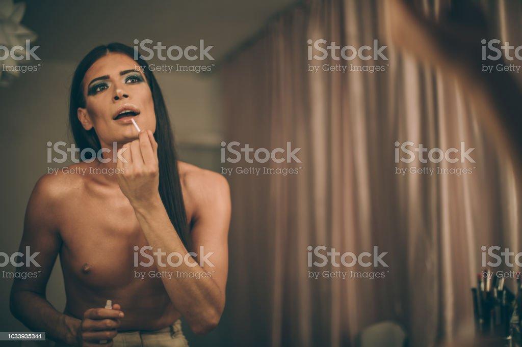 Transsexual man puttinglipstick stock photo