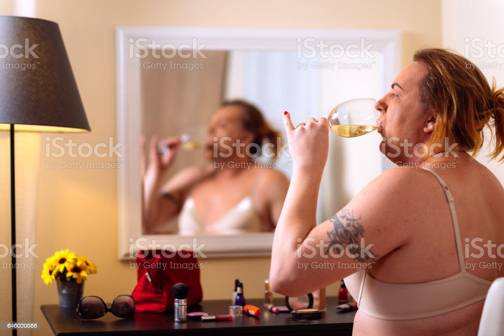 Transsexual person putting make up on in front of the mirror at home stock photo