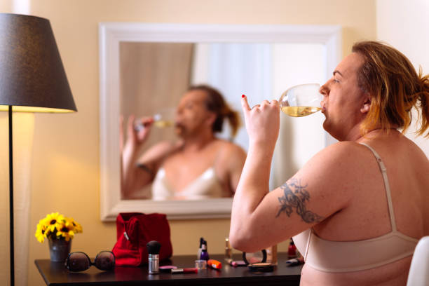 transsexual person putting make up on in front of the mirror at home - transvestite stock photos and pictures