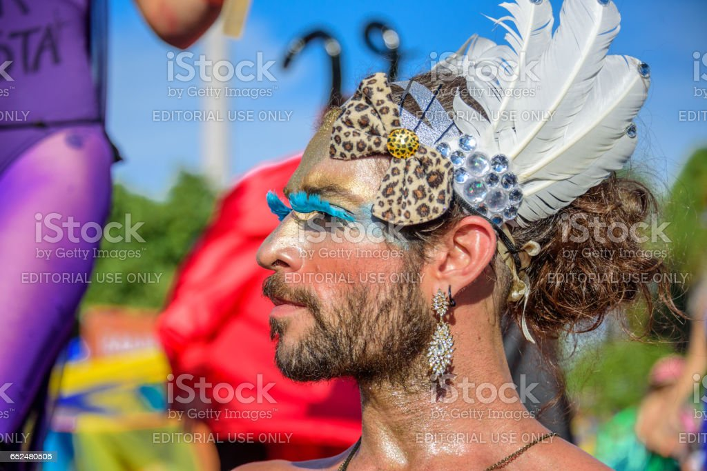Transsexual with enormous blue eyelashes, earrings, headband with leopard bow and feathers, Bloco Orquestra Voadora, Carnaval 2017 stock photo