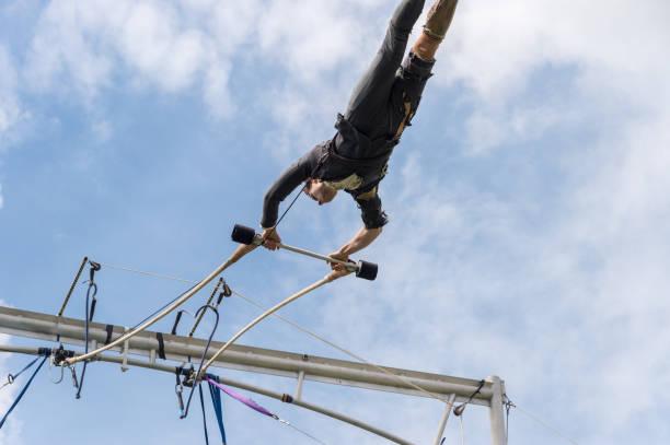 trapezkünstler, die durchführung von außerhalb - trapez stock-fotos und bilder