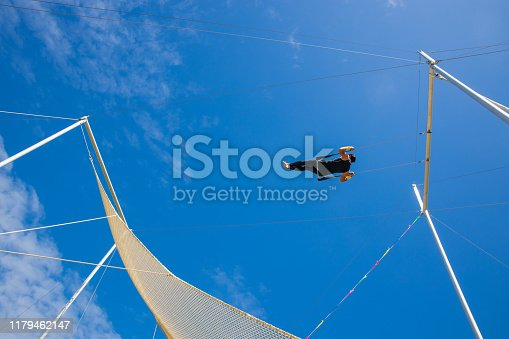 Trapeze artist swinging in the blue sky