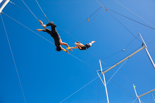 Trapeze artists flying in the blue sky
