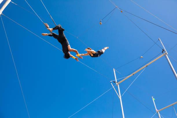 trapezkünstler fliegen am blauen himmel - reliability stock-fotos und bilder
