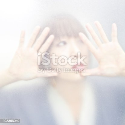 young woman behind milky glass.