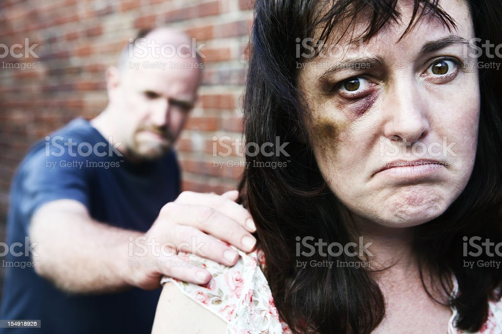 Trapped in an abusive relationship, battered woman tries to escape. stock photo