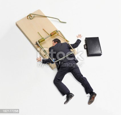 Businessman trapped on mousetrap on white background.