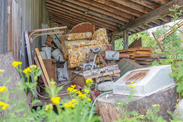 Trash area with vintage materials under old shed in rural Minnesota Trash area with old couch, chairs, motor, and other random antique household materials under old shed in rural Minnesota greed stock pictures, royalty-free photos & images