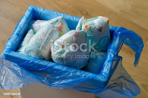 istock trash bin full of used diapers on the wooden floor 1058756426
