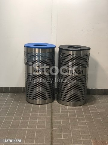 A trash can stands next to a reciting can in a hallway