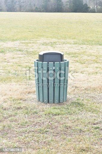 A trash can/rubbish bin sits in a field