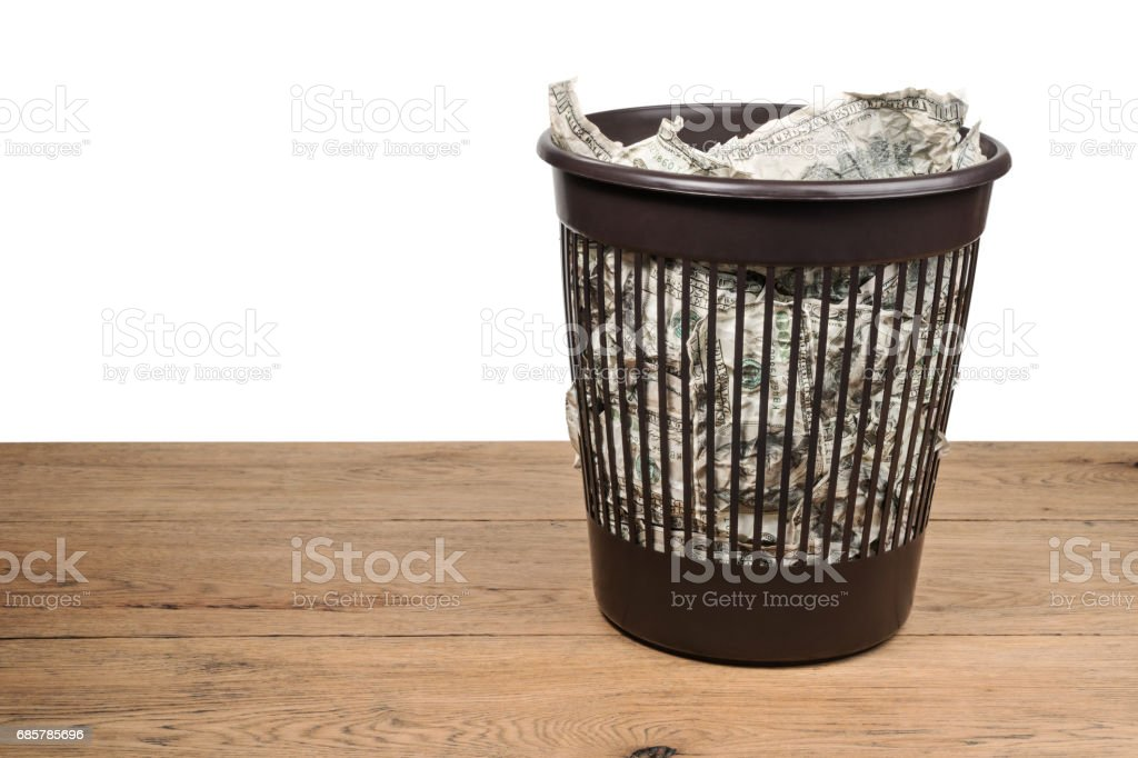 Trash can with crumpled money royalty-free stock photo