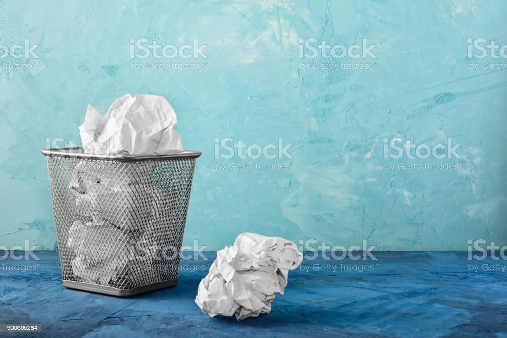A trash can with papers, one lump is lying next to it. Beautiful unusual background with place for text. stock photo