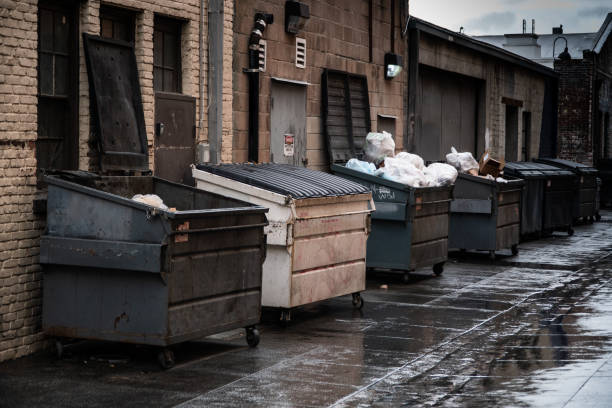 Trash Dumpsters Alley way lined with opened and closed industrial sized trash dumpsters. alley stock pictures, royalty-free photos & images