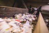 Trash moving on a conveyor belt, blurred motion.