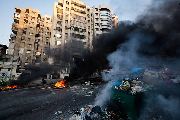 Trash on fire in central Beirut, Lebanon. Beirut, Lebanon - July 25, 2015: People in central Beirut are burning trash and tires as a protest after the government failed to find a solution on where to dump the garbage. And also the contract between the government and the garbage collector Sukleen has come to and end. The garbage has piled up on the streets of Beirut and Mount Lebanon for more then a week today. dumpster fire stock pictures, royalty-free photos & images