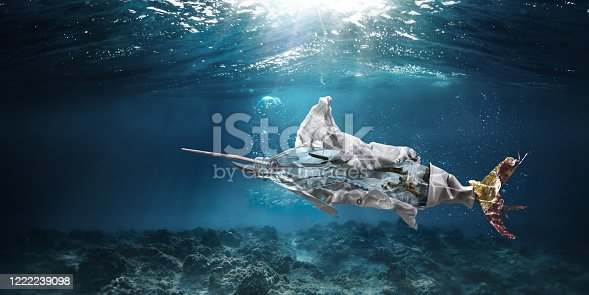 A conceptual image showing one of the most common types of trash found in the ocean - cigarettes, plastic bottles, plastic bags, straws, food packaging, ring pull and plastic cutlery - in the shape of a marlin or swordfish, falling to the bottom of the ocean. Set underwater with copy space.