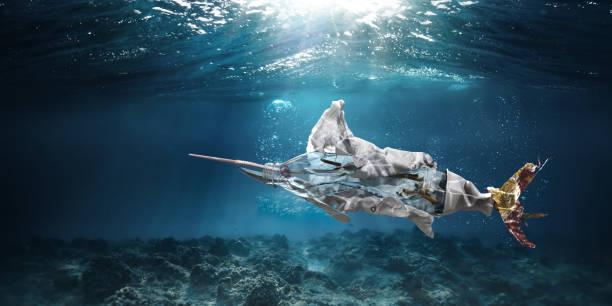 trash underwater in ocean in shape of marlin swordfish - ocean plastic stock pictures, royalty-free photos & images