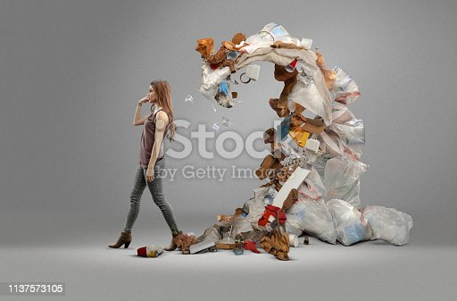 Woman tossing trash over her shoulder, only to have it come back ten folds